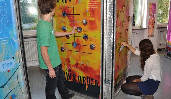 Zwei Jugendliche an einer Lernwand