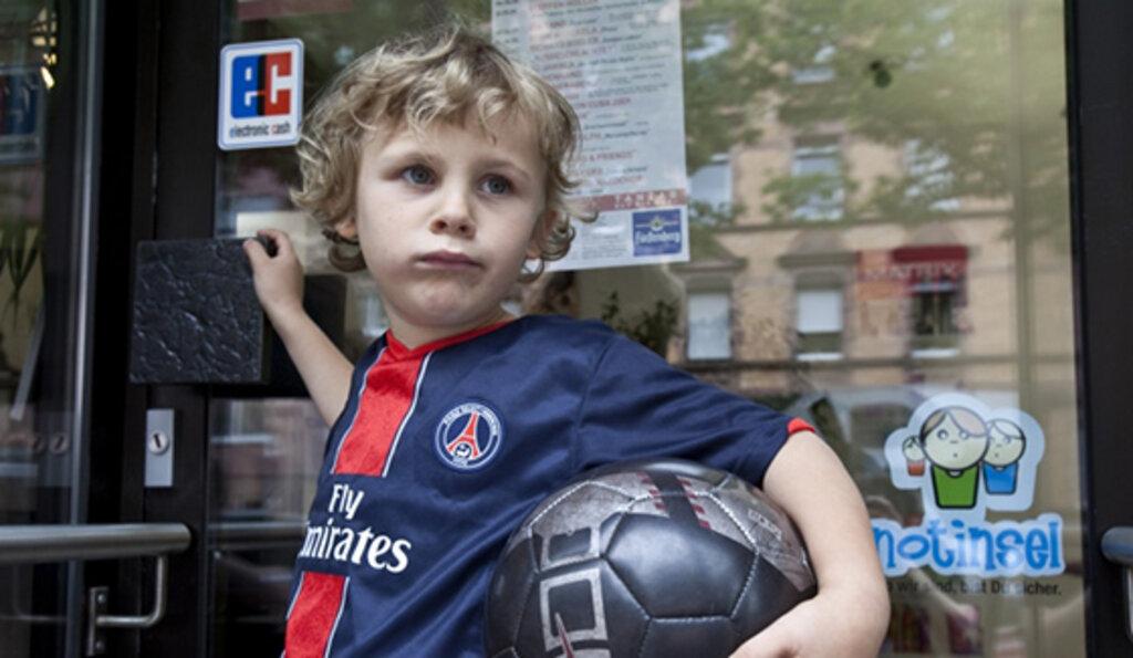 Junge steht vor Tür mit Notinsel Aufkleber