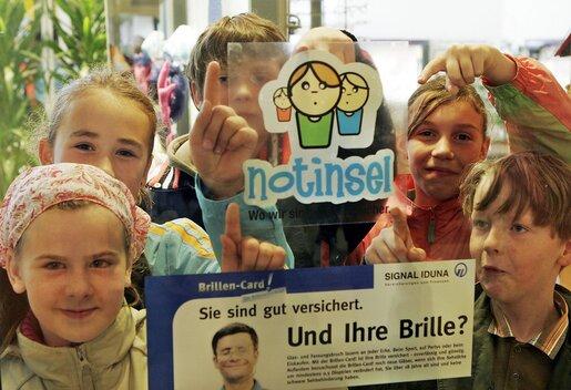 Kinder halten Notinselschild in die Luft