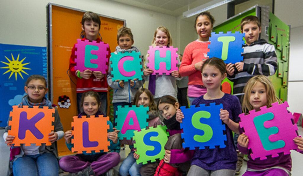 Kinder halten Puzzle Teile mit Echt Klasse Schrift hoch