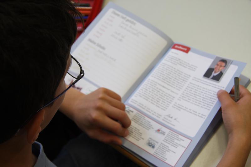 Ein Schüler liest sich aufmerksam das Hausaufgabenheft durch